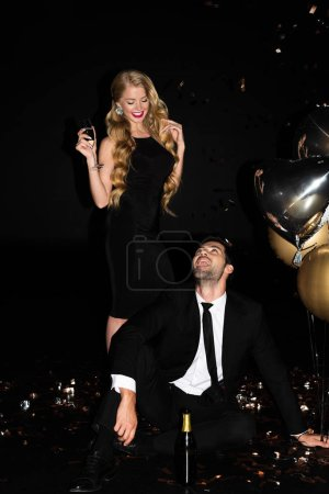 Foto de Young couple drinking champagne and celebrating with balloons and golden confetti on black - Imagen libre de derechos