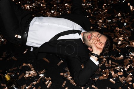 Photo for Fashionable man lying on floor with golden confetti for holiday - Royalty Free Image