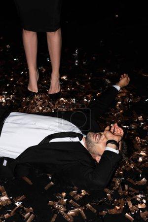 Photo pour Jeune homme couché sur des confettis dorés tandis que la petite amie debout près de noir - image libre de droit