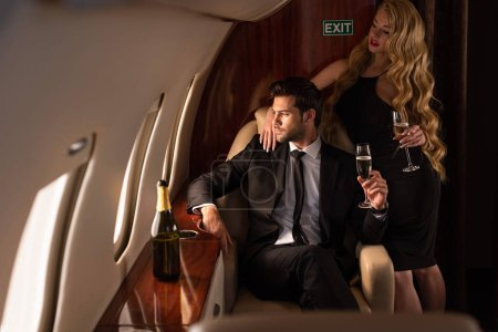 Photo for Elegant fashionable with champagne traveling in plane - Royalty Free Image