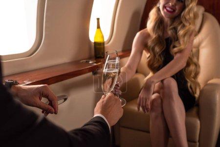 Photo pour Vue en coupe d'un beau couple clinking avec des verres de champagne en voyageant en avion - image libre de droit