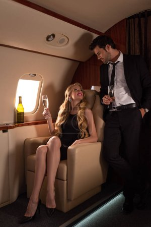 Photo for Beautiful elegant couple drinking champagne together while traveling in plane - Royalty Free Image