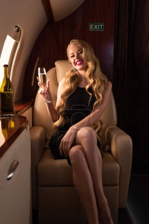 sensual smiling woman with champagne sitting in plane