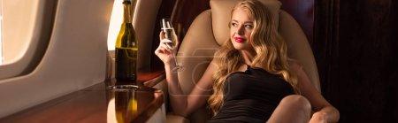 schöne blonde Frau mit Champagner sitzt im Flugzeug