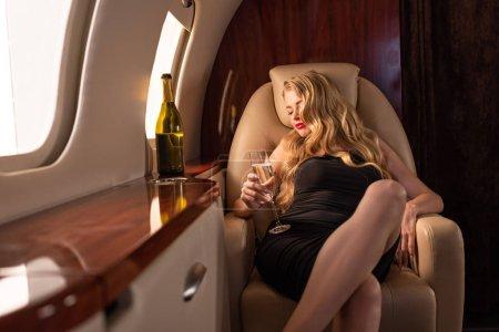 Photo pour Belle femme glamour dormant avec du champagne assise dans l'avion - image libre de droit
