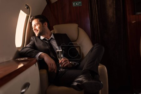 Photo for Handsome man holding glass of champagne in aircraft - Royalty Free Image