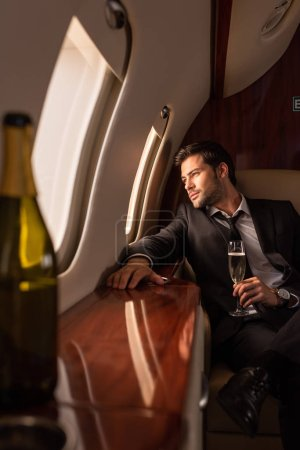 Photo for Dreamy man holding glass of champagne in plane, selective focus of bottle - Royalty Free Image