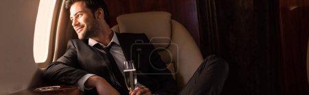 Photo pour Bel homme joyeux tenant un verre de champagne dans l'avion - image libre de droit