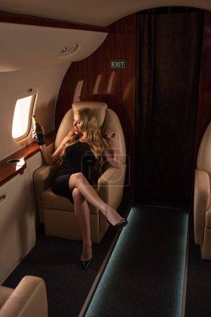 Photo pour Happy glamorous femme avec champagne assise en avion - image libre de droit