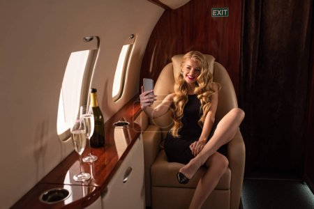 Photo pour Sexy attractive woman taking selfie on smartphone with champagne in airplane - image libre de droit