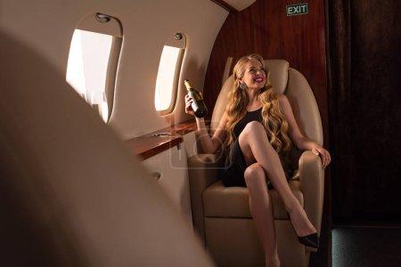 Photo pour Passionnée belle femme avec champagne assis dans l'avion - image libre de droit