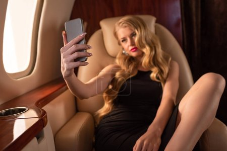 Photo pour Une femme passionnée se prend sur un smartphone avec du champagne en avion - image libre de droit