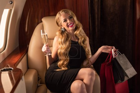 Photo for Sexy blonde woman with shopping bags and champagne in aircraft - Royalty Free Image