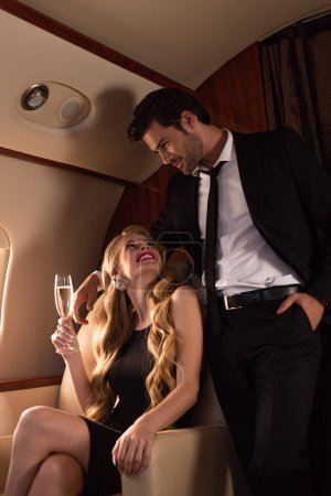 Photo for Beautiful elegant couple drinking champagne while traveling in plane - Royalty Free Image