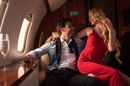 Photo pour Beau couple avec champagne assis dans l'avion - image libre de droit