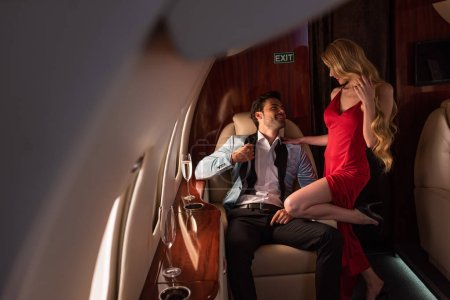 Photo pour Beautiful sexy couple with champagne sitting in airplane - image libre de droit