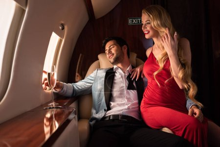 Photo for Beautiful elegant couple with champagne sitting in airplane - Royalty Free Image
