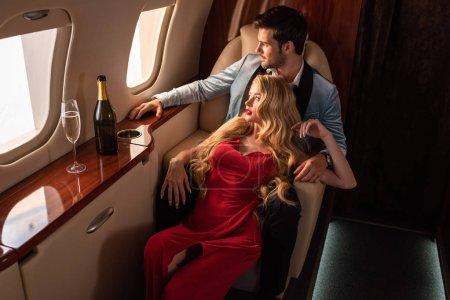 Foto de Hermosa pareja seductora con champán sentado en el avión - Imagen libre de derechos