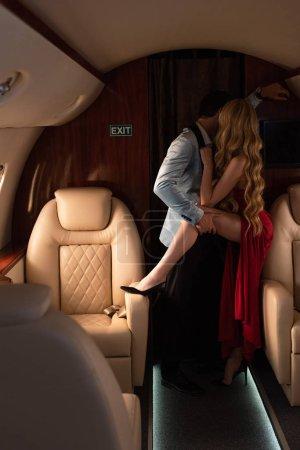 Foto de Handsome sexy man hugging and kissing girlfriend in airplane - Imagen libre de derechos