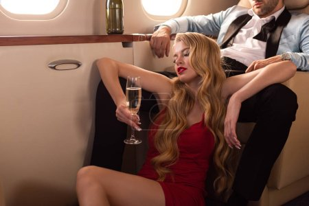 Photo for Beautiful passionate couple with champagne sitting in airplane - Royalty Free Image