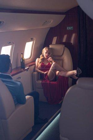 Foto de Beautiful elegant sexy couple sitting in airplane - Imagen libre de derechos