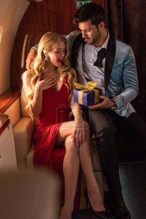 Photo for Man presenting gift box to sexy woman in plane - Royalty Free Image