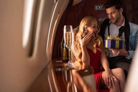 Photo for Man presenting gift box to sexy woman in plane with champagne - Royalty Free Image