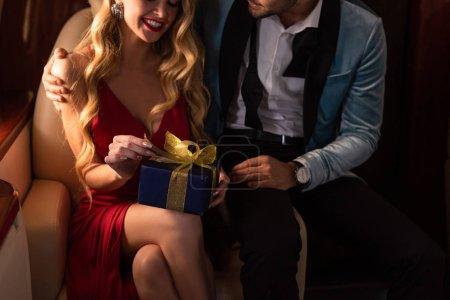 Photo for Happy man presenting gift box to sexy woman in plane - Royalty Free Image