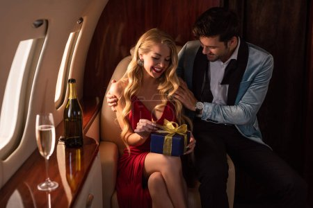 Photo for Handsome man presenting gift to attractive sexy woman in plane - Royalty Free Image