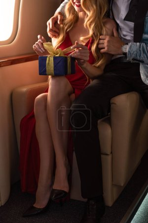 Photo for Cropped view of couple with present in plane - Royalty Free Image