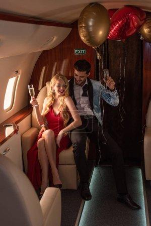 Foto de Beautiful young couple with champagne sitting in airplane - Imagen libre de derechos