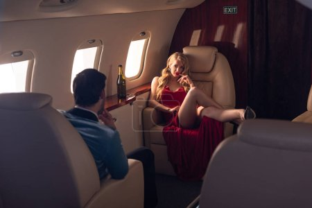 Photo pour Sexy girlfriend and boyfriend with champagne sitting in airplane - image libre de droit