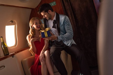 Photo for Man presenting gift box to happy blonde woman in plane - Royalty Free Image