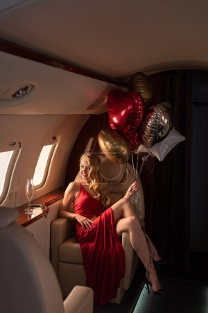 Photo pour Sexy attractive woman with champagne and ballons sitting in plane - image libre de droit