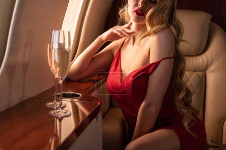 Photo pour Crochet vue d'une femme sexy glamour avec champagne assise en avion - image libre de droit