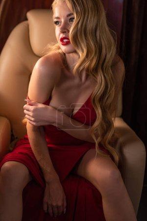 sexy glamouröse Frau im roten Kleid sitzt im Flugzeug