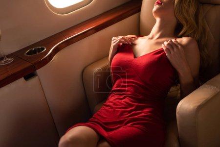 Foto de Cropped view of sexy woman in red dress sitting in plane - Imagen libre de derechos