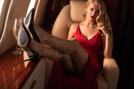 Foto de Seductora chica rubia en vestido rojo sentado en avión - Imagen libre de derechos