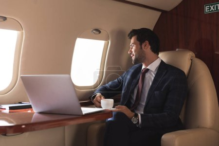 Photo for Pensive businessman holding cup of coffee in plane with laptop during business trip - Royalty Free Image