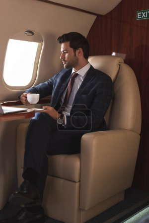 Photo for Serious businessman in suit drinking coffee in airplane during business trip - Royalty Free Image
