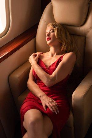 Foto de Sexy woman in red dress lying in plane - Imagen libre de derechos