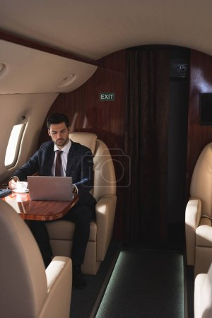 Photo for Handsome businessman working on laptop in plane during business trip - Royalty Free Image