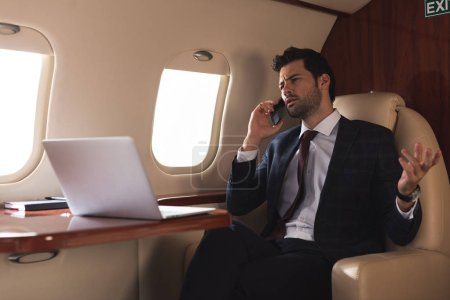 manager talking on smartphone in plane with laptop during business trip