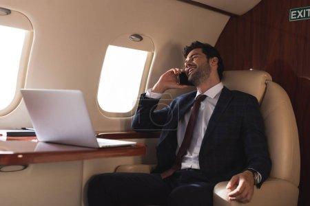 Foto de Laughing businessman talking on smartphone in plane with laptop during business trip - Imagen libre de derechos
