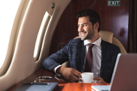 Photo for Smiling businessman holding cup of coffee in plane during business trip - Royalty Free Image