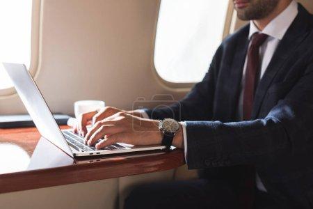 Photo pour Vue recadrée de l'homme d'affaires tapant sur un ordinateur portable dans un avion pendant un voyage d'affaires - image libre de droit