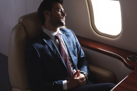 Photo for Businessman sleeping in airplane during business trip - Royalty Free Image