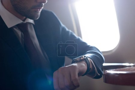 cropped view of businessman looking at watch while sitting in airplane