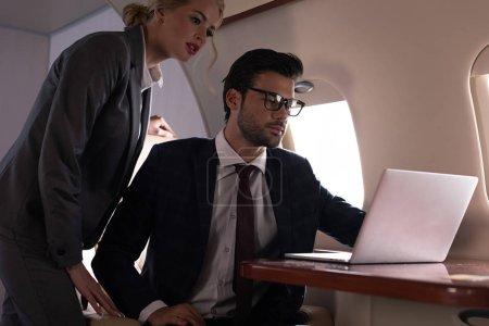 Photo pour Cadres professionnels gens d'affaires travaillant sur un ordinateur portatif assis dans un avion - image libre de droit
