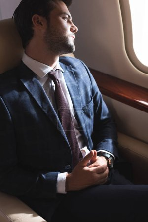 Photo for Pensive businessman looking into window in plane - Royalty Free Image
